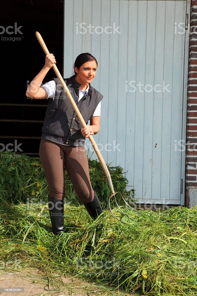 young woman on a farm with hayfork stock photo