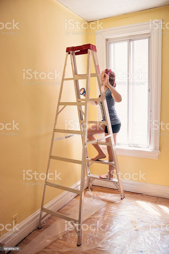Young woman on a ladder getting room ready to re-paint. stock photo