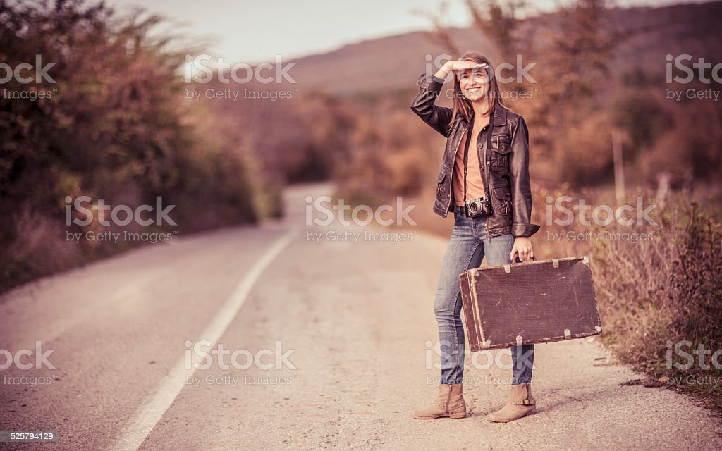 Young woman on a road trip hitchhiking stock photo