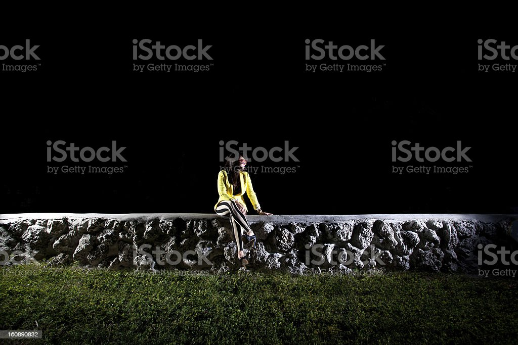 Young Woman on a stone wall at night by herself royalty-free stock photo