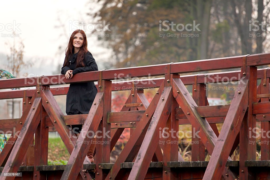 Young woman on a wooden footbridge. stock photo