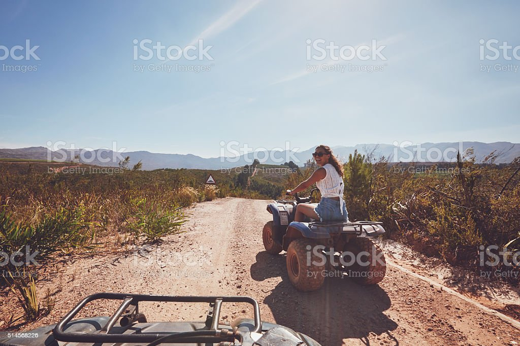 Young woman on an all terrain vehicle in nature stock photo