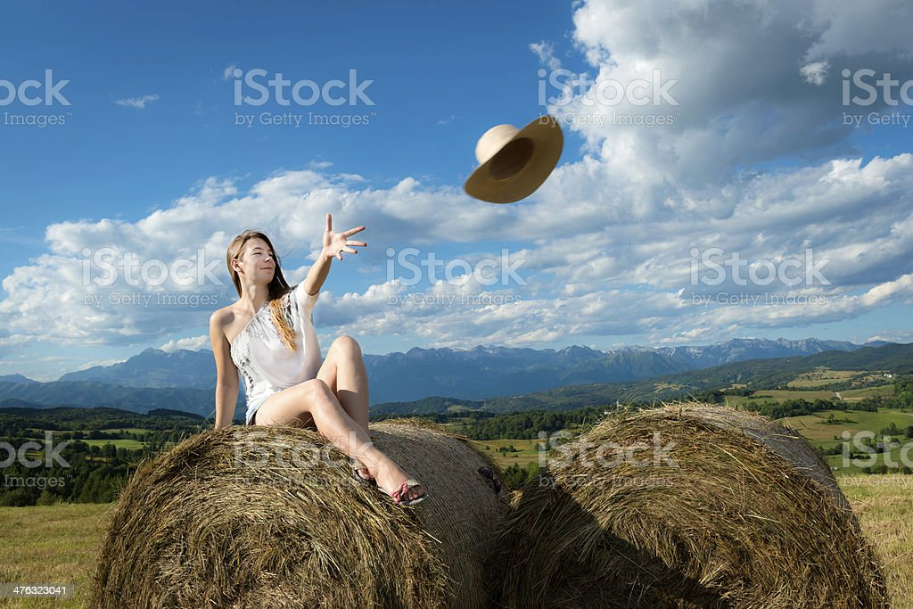 Young Woman on Bale Silage Throwing Straw Hat royalty-free stock photo