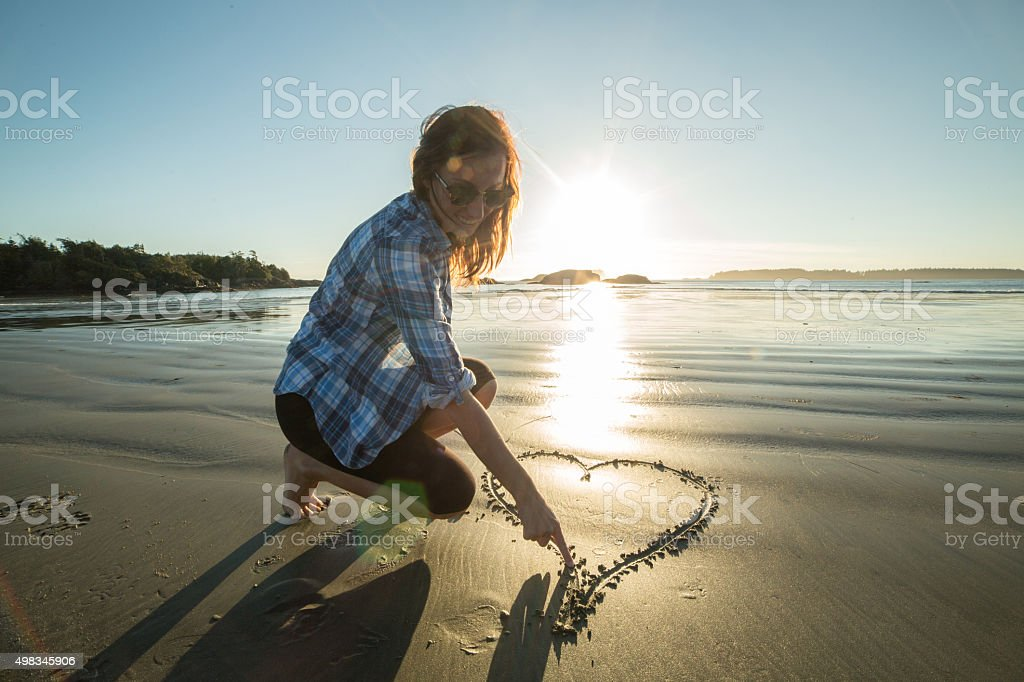 Young woman on beach drawing heart shape on sand-sunset stock photo