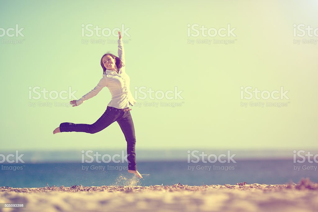 young woman on beach jumping with arms up stock photo