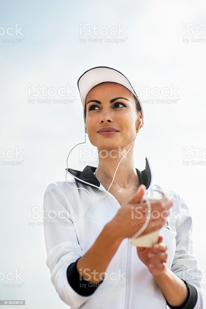 Young woman on beach listening to music stock photo