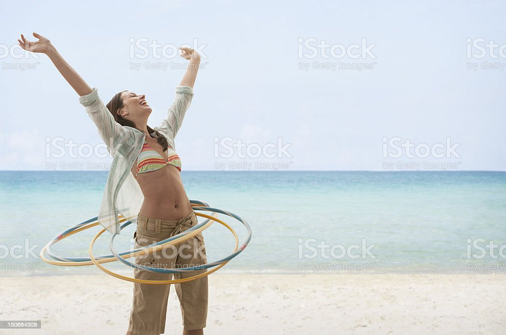 Young woman on beach playing with hula hoops stock photo