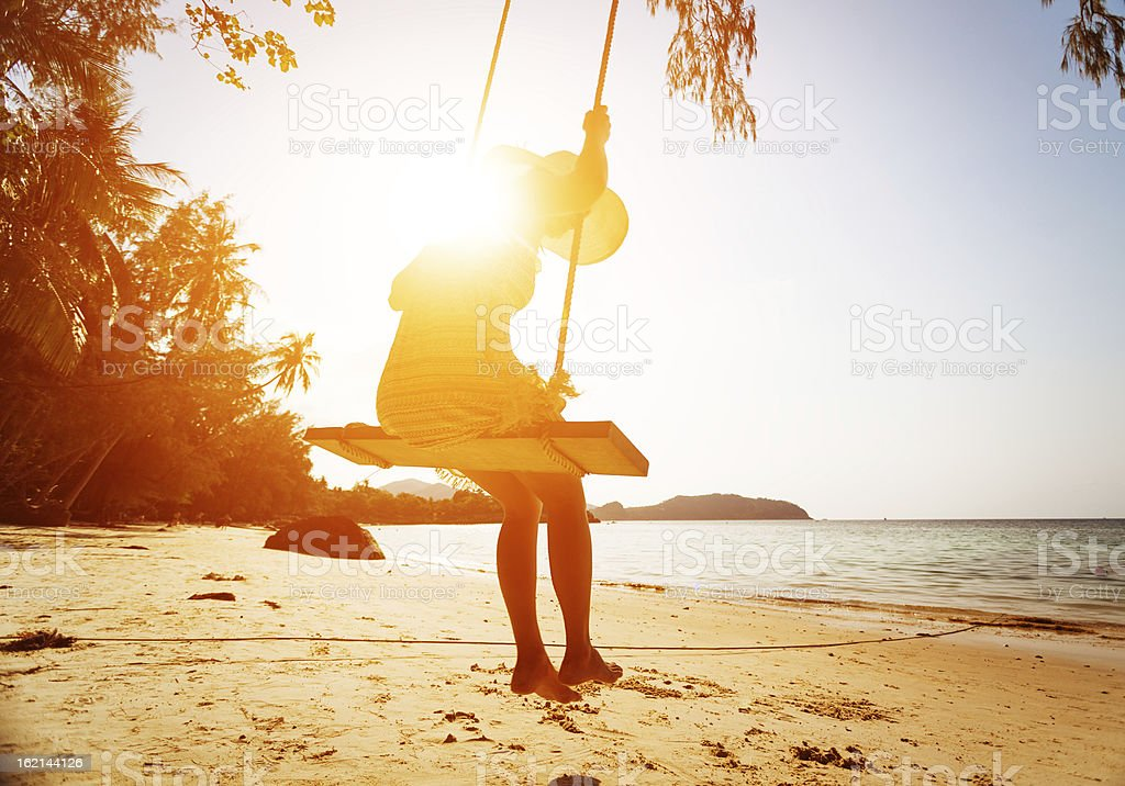 young woman on beach swing stock photo