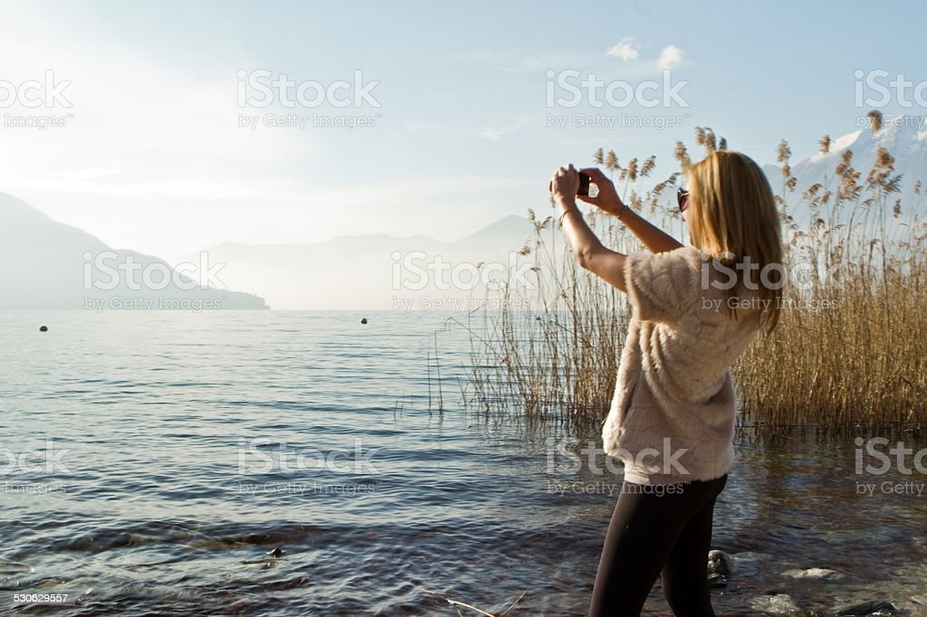 Young woman on beach takes picture with smart phone stock photo