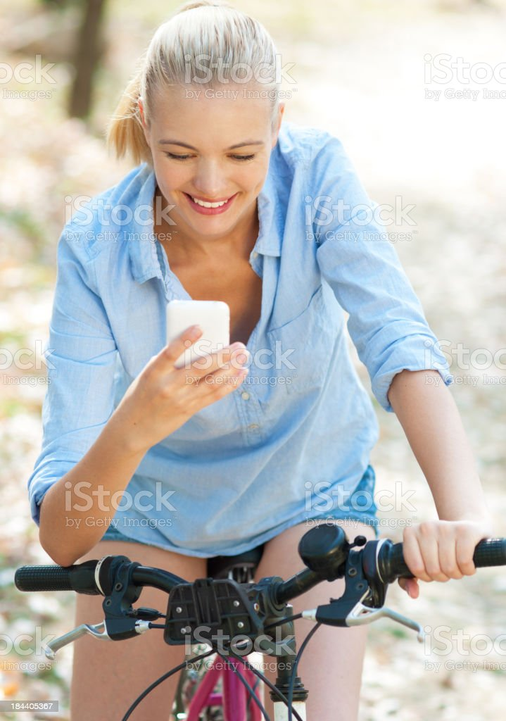 young woman on bike typing text message royalty-free stock photo