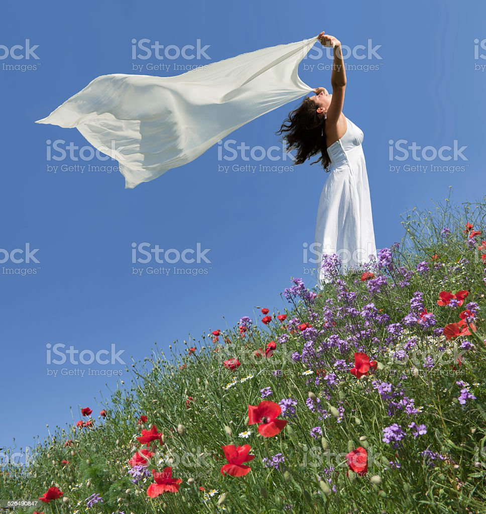 Young woman on blooming meadow holding white scarf in wind stock photo