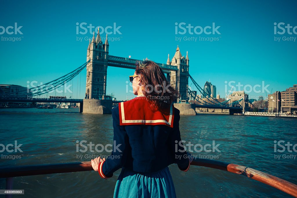 Young woman on boat looking at Tower Bridge in London stock photo