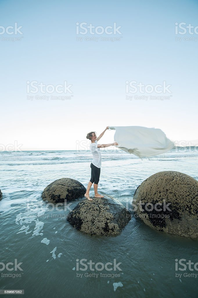 Young woman on boulder holds blanket in the air stock photo