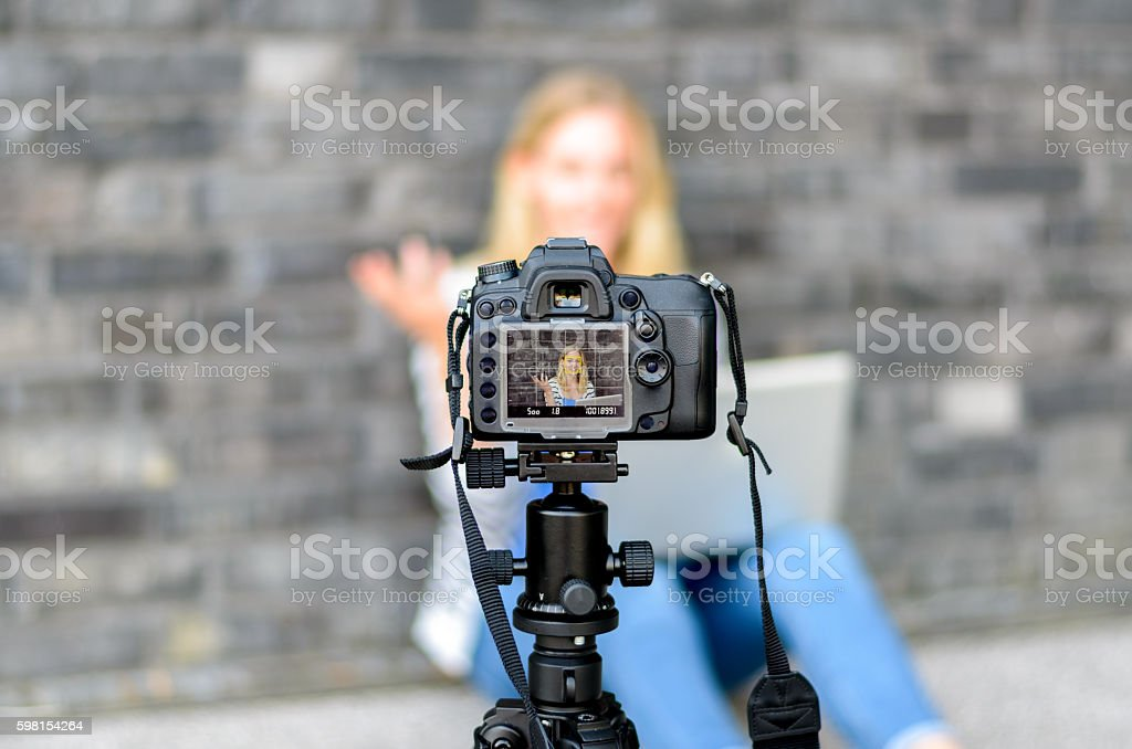 Young woman on camera LCD screen waving stock photo
