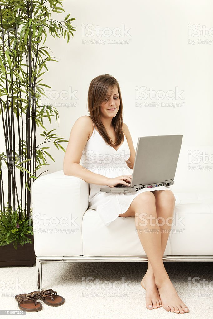 Young Woman on Couch with Laptop stock photo