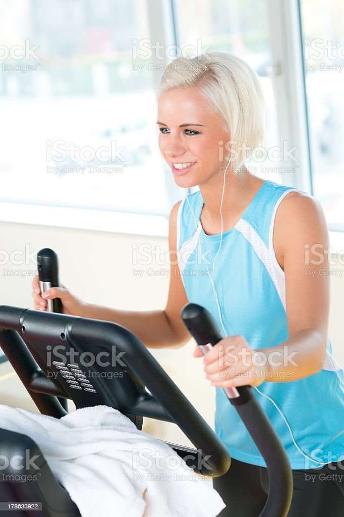 Young woman on fitness machine cardio exercise stock photo