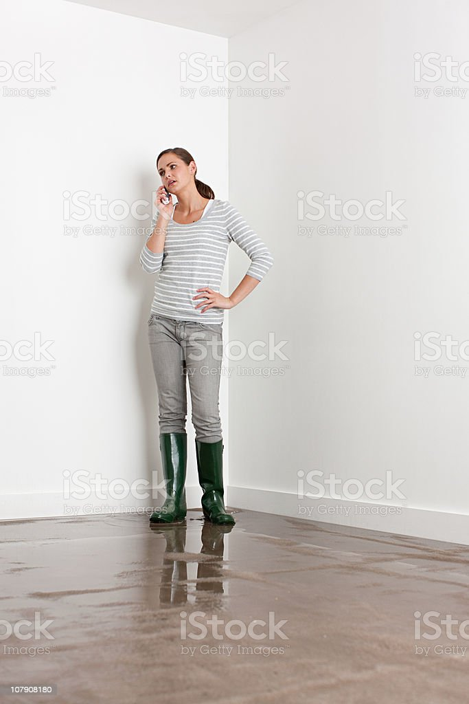 Young woman on flooded floor stock photo