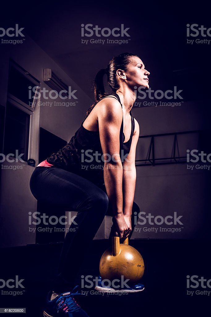 Young woman on gym training with kettlebell in gym stock photo