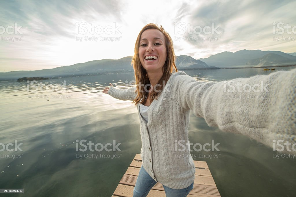 Young woman on jetty above lake, takes selfie portrait stock photo