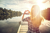 Young woman on lake pier makes heart shape finger frame