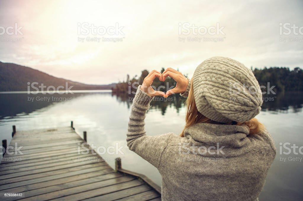 Young woman on lake pier, makes heart shape finger frame – Foto