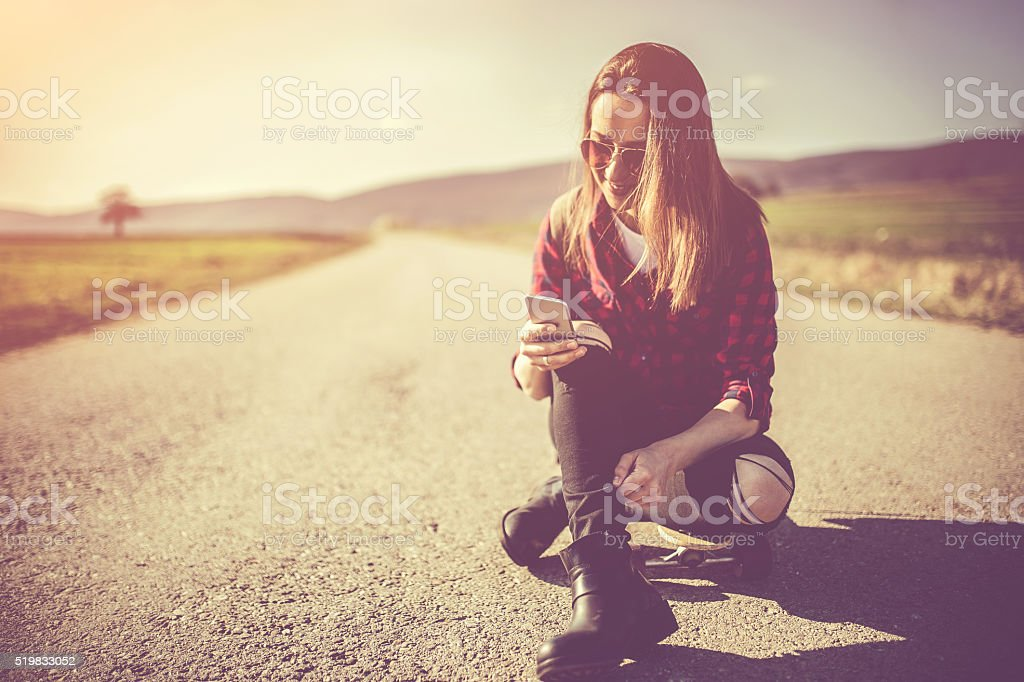 Young  woman on longboard making selfie stock photo