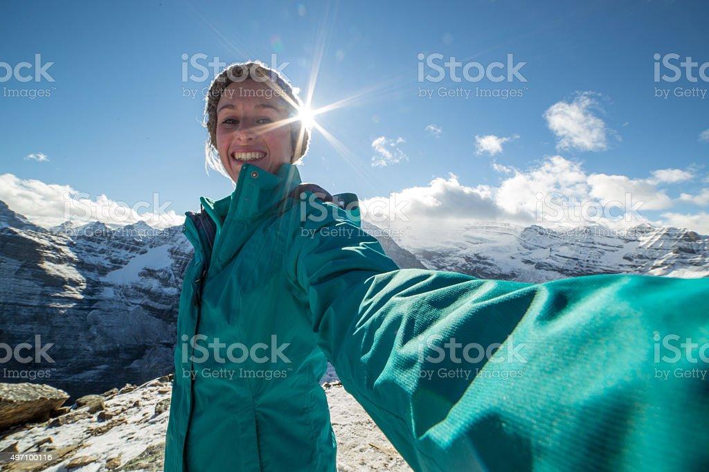 Young woman on mountain peak takes a selfie portrait stock photo