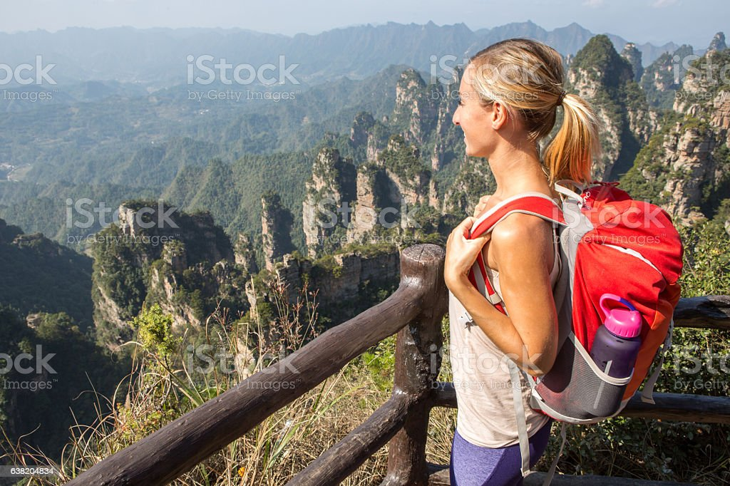 Young woman on mountain top contemplating nature stock photo