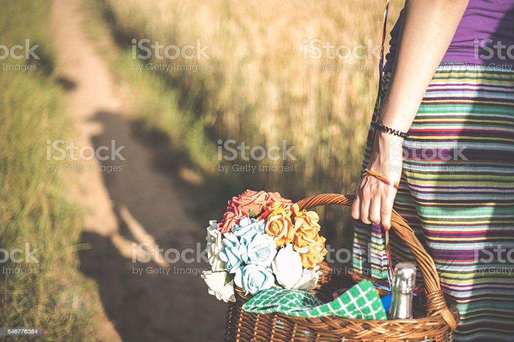 young woman on nature with a basket of flowers