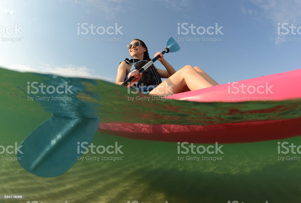 Young woman on ocean in kayak stock photo