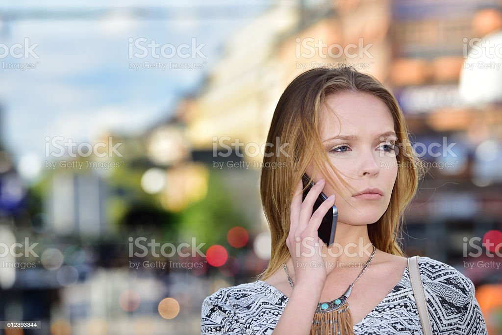Young woman on phone, central Stockholm in background stock photo