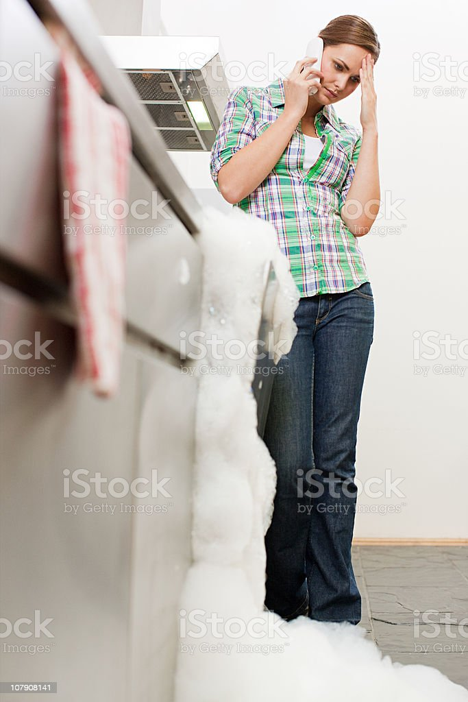 Young woman on phone with overflowing dishwasher stock photo