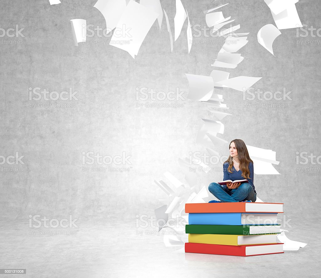 young woman on  pile of books with paper flying around stock photo