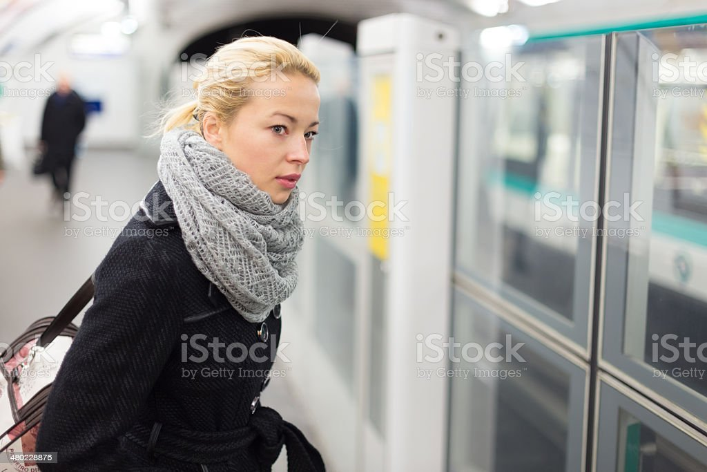 Young woman on platform of metro station. stock photo