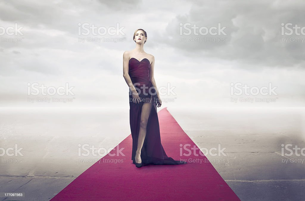 Young woman on red carpet with cloud background stock photo
