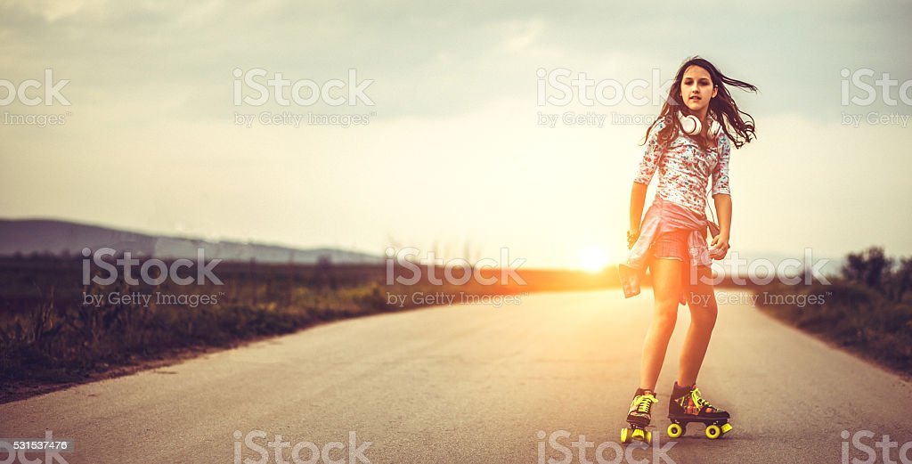 Young woman on roller skates skating into sunset stock photo
