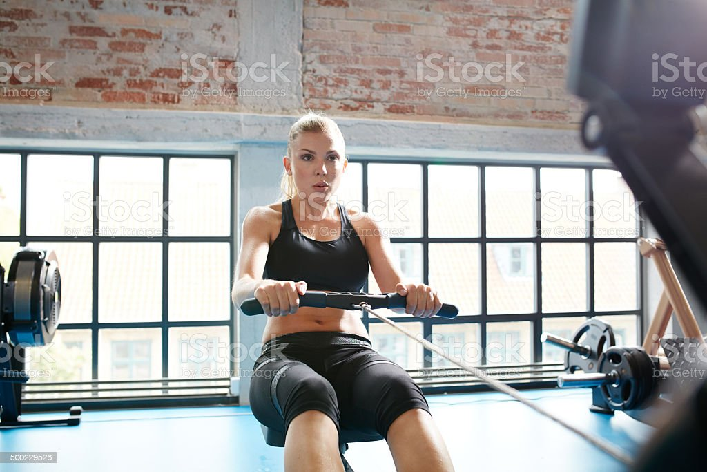 Young woman on rowing machine stock photo