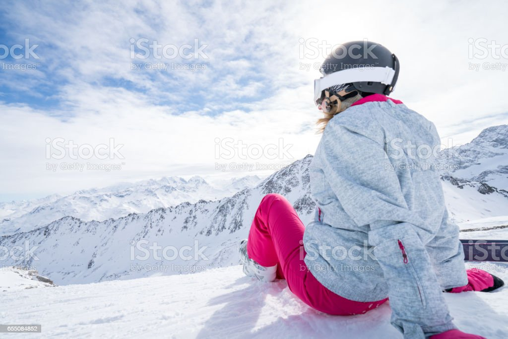 Young woman on ski slopes looking at view stock photo