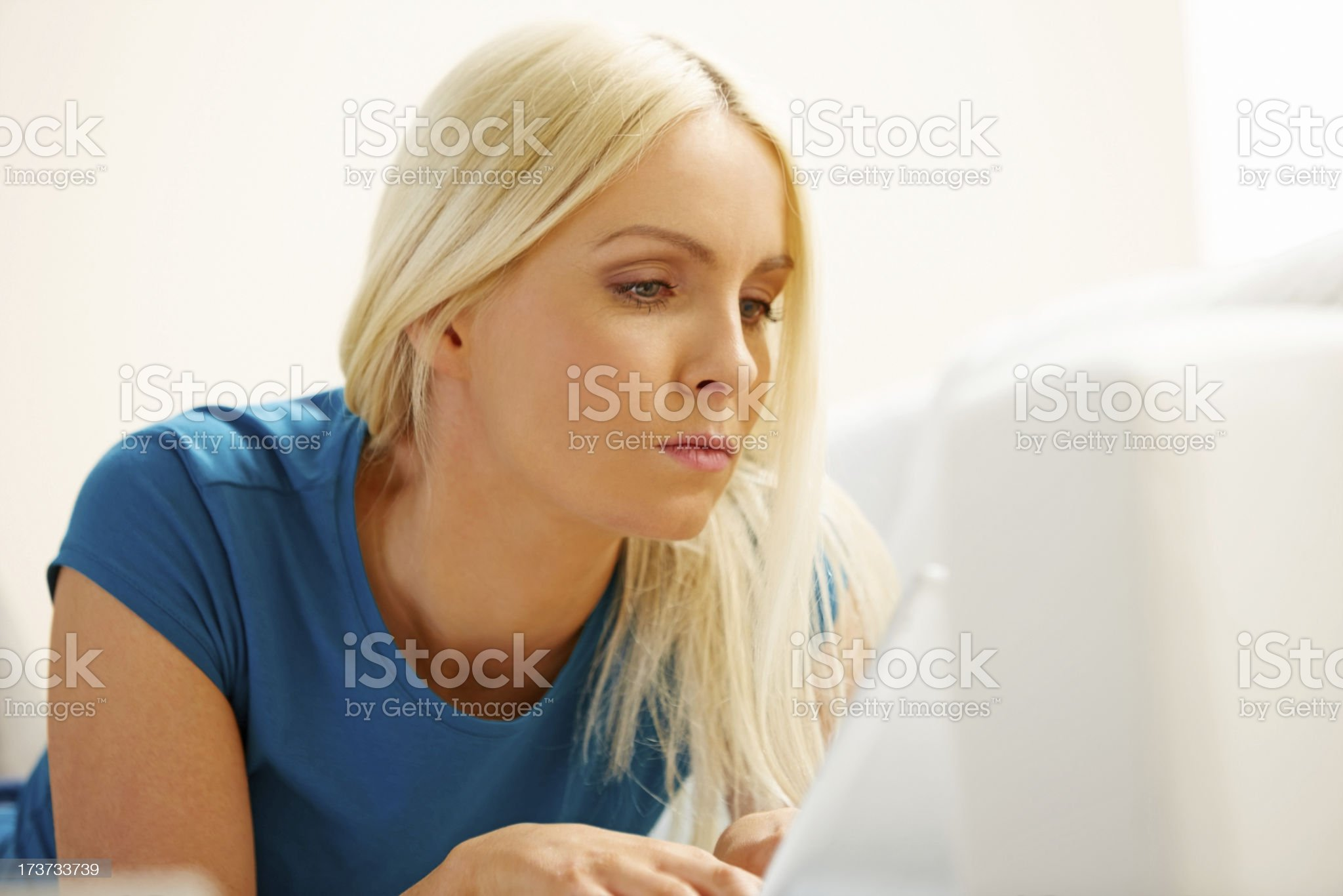 Young woman on sofa using laptop computer at home royalty-free stock photo