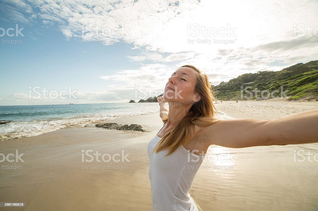 Young woman on the beach arms outstretched for positive emotion stock photo