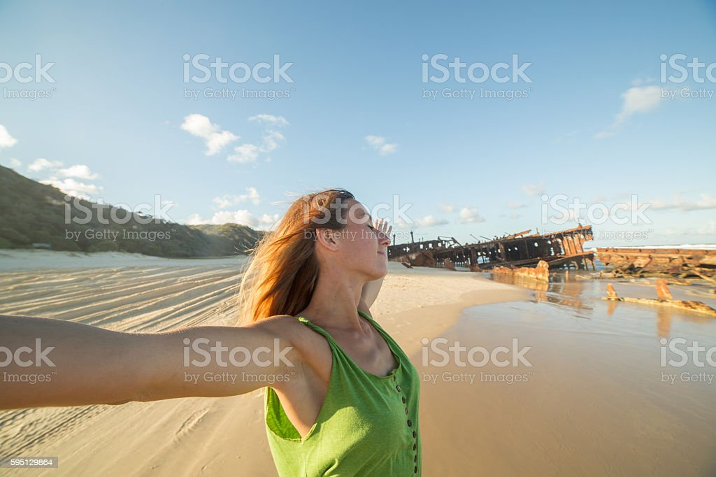 Young woman on the beach at sunset outstretches arms stock photo