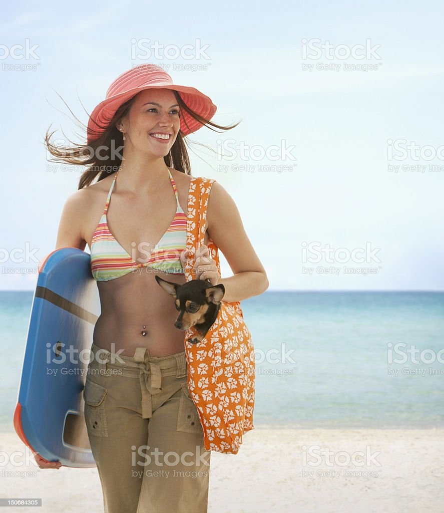 Young woman on the beach holding small dog and boogie board royalty-free stock photo