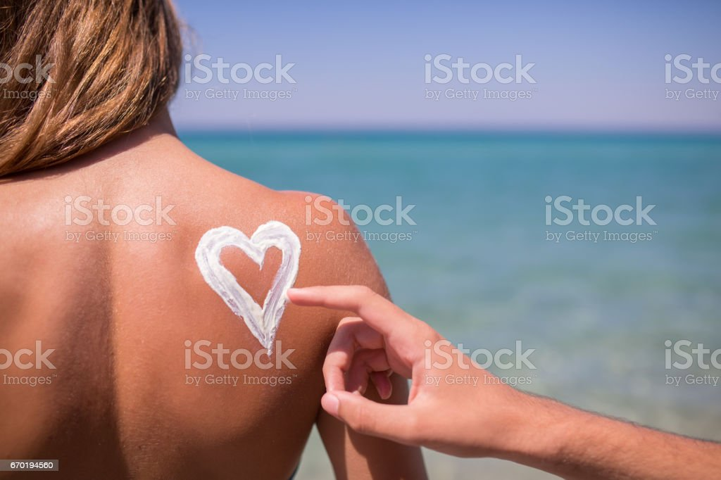 Young woman on the beach with sun protective lotion stock photo