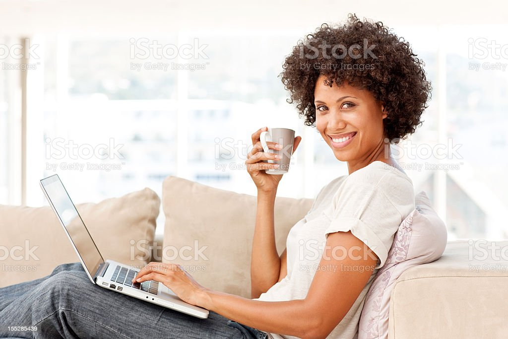 Young Woman on the Couch With a Laptop royalty-free stock photo