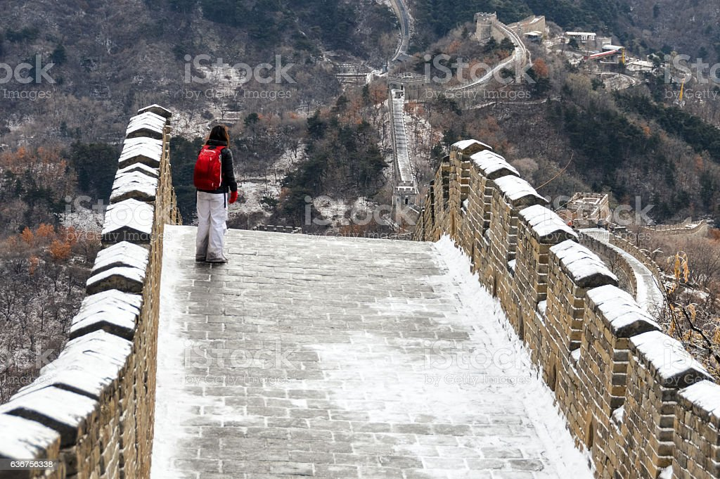 Young woman on the Great Wall of China with snow stock photo
