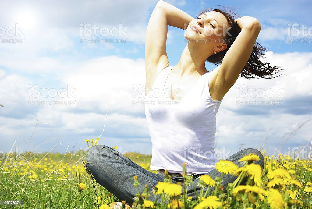 Young woman on the meadow dreaming. stock photo