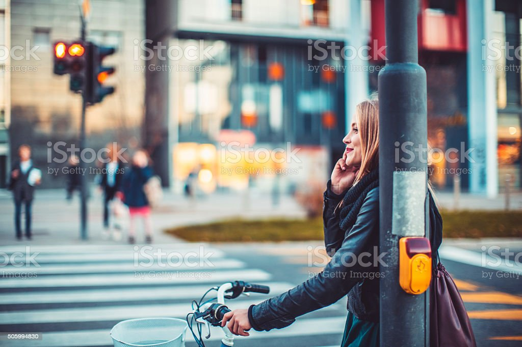 Young woman on the phone, street, sunset stock photo