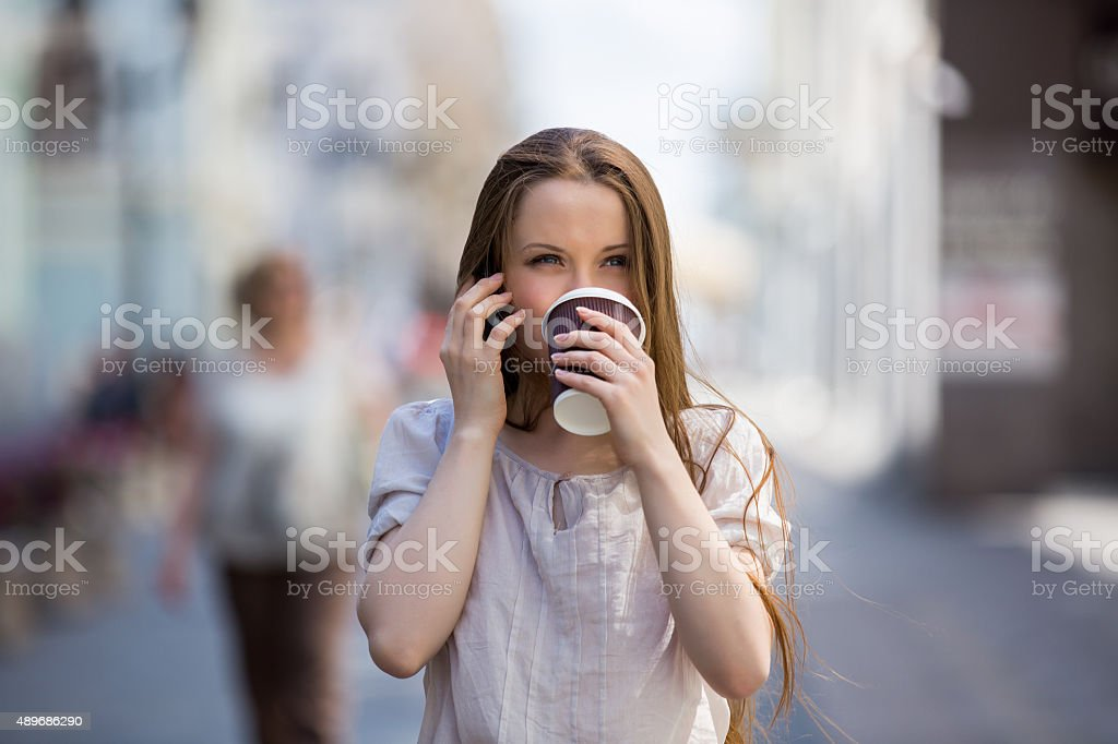 Young woman on the street drinking coffee stock photo