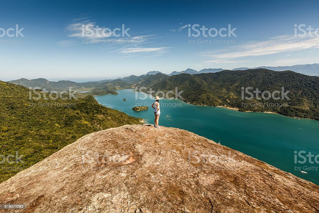 Young Woman on Top of High Mountain on Sunny Morning stock photo