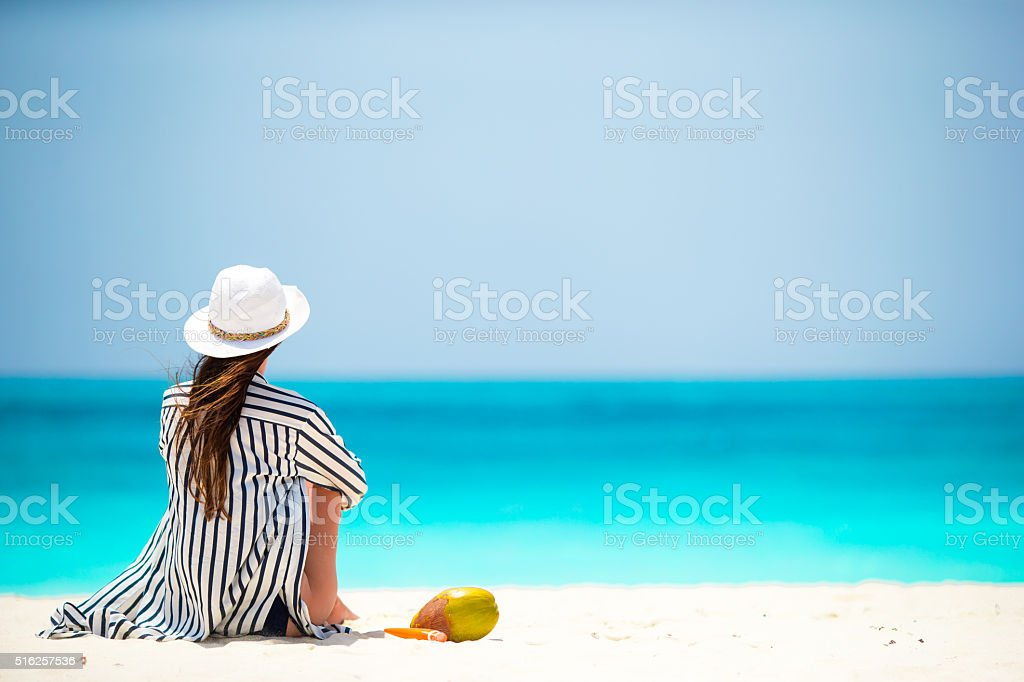 Young woman on white beach with coconut stock photo